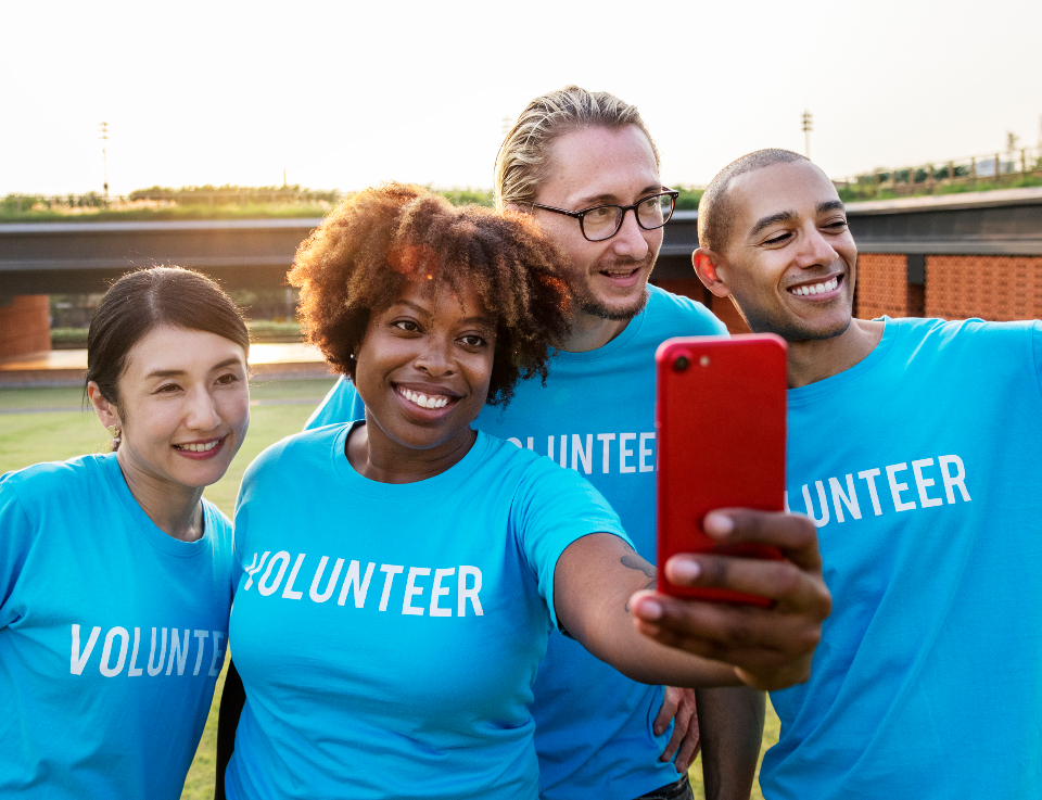 blue capturing cheerful community community service digital device diverse donation enjoy friendship happiness kindness man organization outdoors park group charity mobile phone
