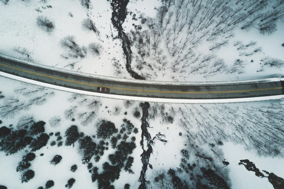 aerial trees snow path road lane mountain highlands branches travel adventure