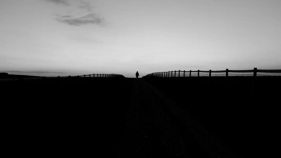 man woman people street road path fences baluster sky silhouette light shadows black and white lines patterns