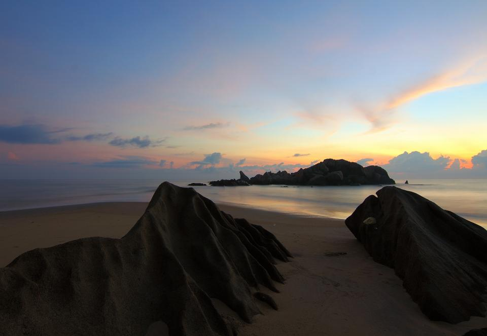 beach sand sea water rock formation nature sky clouds sunset