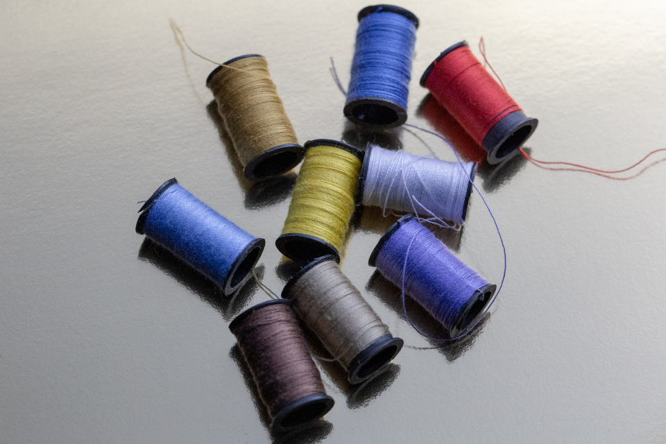 sewing thread spools colors stitching threads background crafts diy cotton soft focus red blue reflection yellow purple