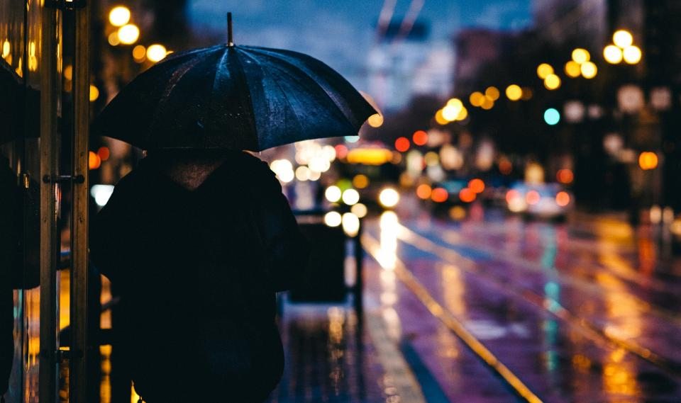 person people back stand umbrella rain drizzle wet reflection street lights traffic buildings city downtown urban metro still bokeh