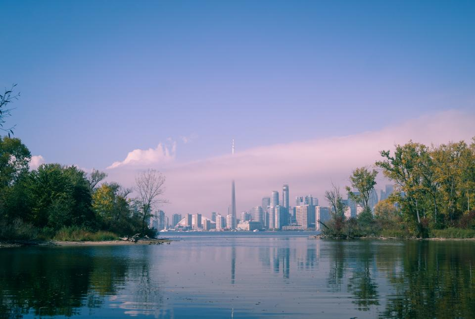 architecture building infrastructure city tower skyline blue sky clouds lake water nature trees plants reflection
