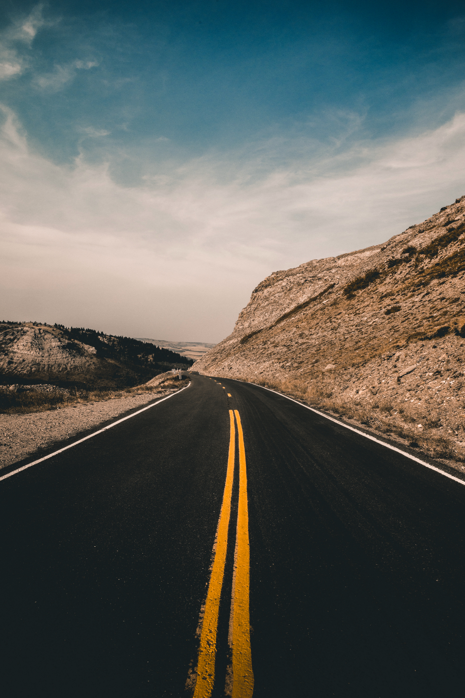 travel road country western west movement travelling traveller driving drive highway pavement desert dirt landscape nature outdoors mountains mountain blue sky clouds montana