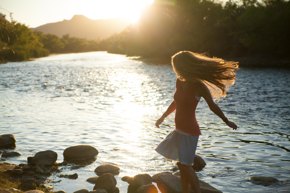 sunset girl river cross sunny sun water stepping stones rock reflection tree forest wood woman people beautiful flow hair red white skirt