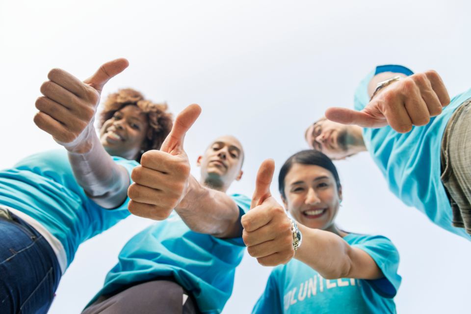 happy people thumbs up gesture afro blue business agreement colleagues charity cheerful smiling community deal diverse excellence friends friendship group hands man woman male female outdoors sky
