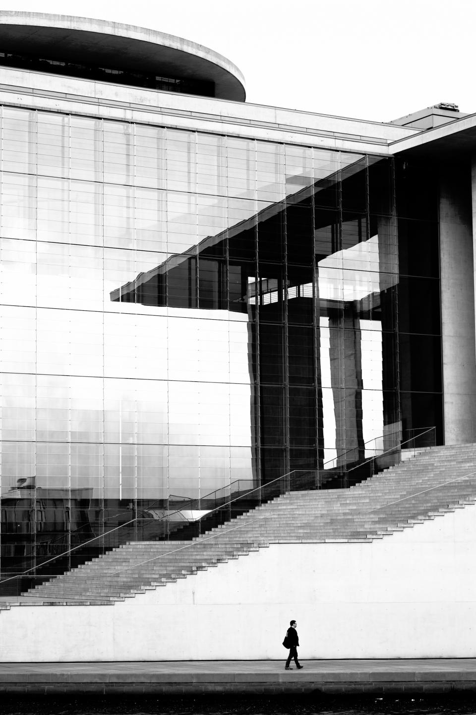 buildings structure architecture design stairs lines glass window people man guy walking black and white grayscale monochrome