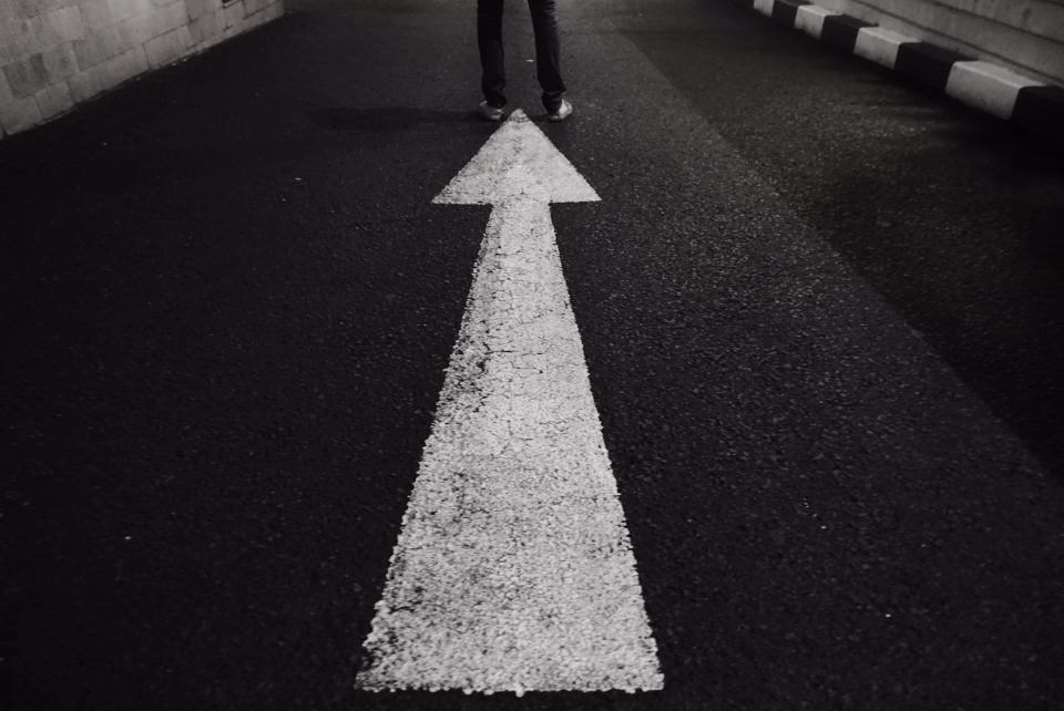 street feet leg arrow direction night standing asphalt pointing up road lane roadway