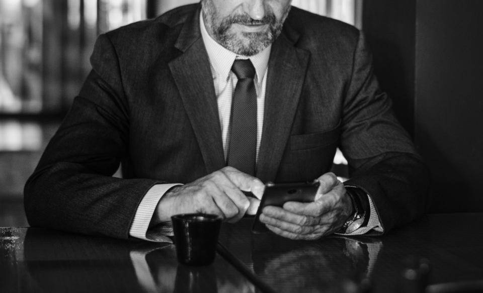 business browsing phone alone person man male beard boss businessman busy ceo corporate focused manager messaging texting news online people reading restaurant meeting suit