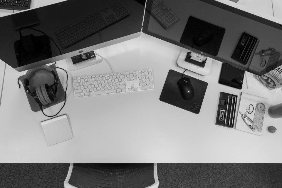mac desktop computer monitors keyboard mouse headphones objects technology business office desk black and white