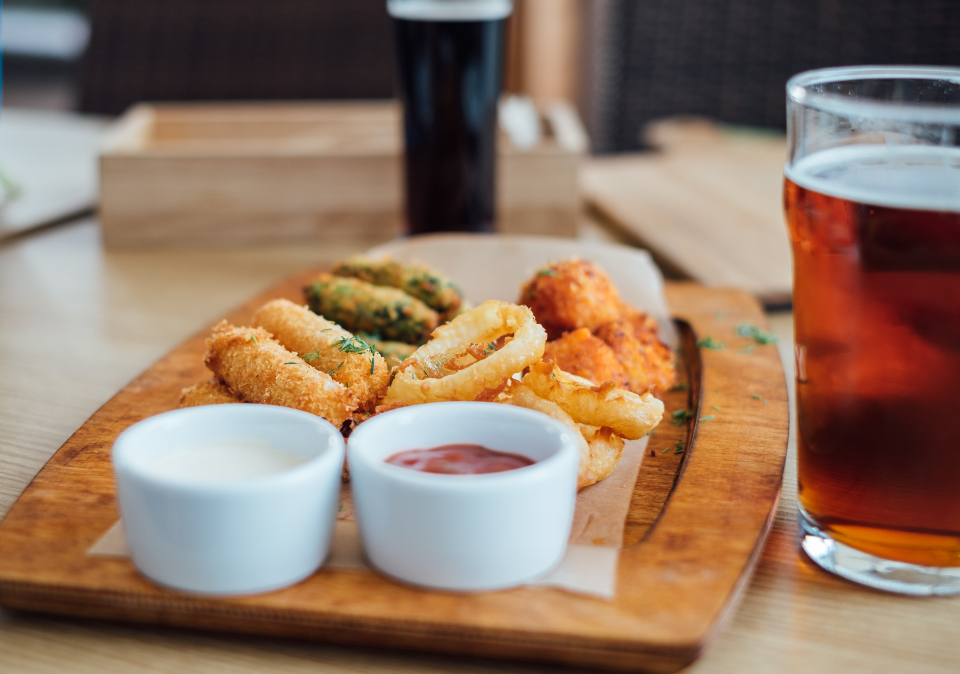 snacks wooden plate beer pint glass white ceramic bowl onion rings tasty food table