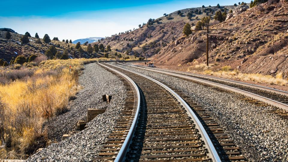 railway track mountain valley trees plant grass nature blue sky clouds landscape travel
