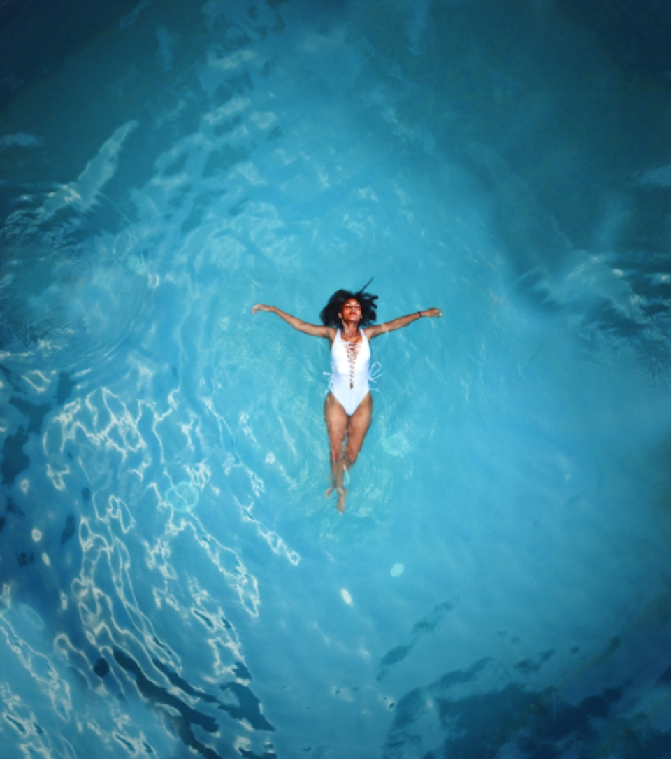 woman swimming alone isolated pool blue white swimsuit dark hair travel vacation happy chilled