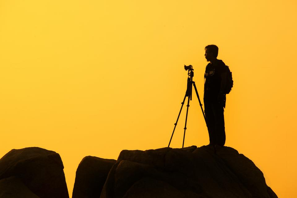 yellow sunset dusk shadow silhouette photographer camera guy man people rocks