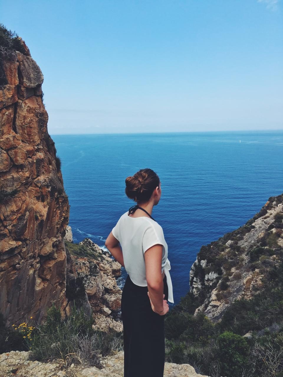 woman girl lady people back stand cliff style fashion outdoors travel mountains rocks bushes plants coast shore water sea ocean