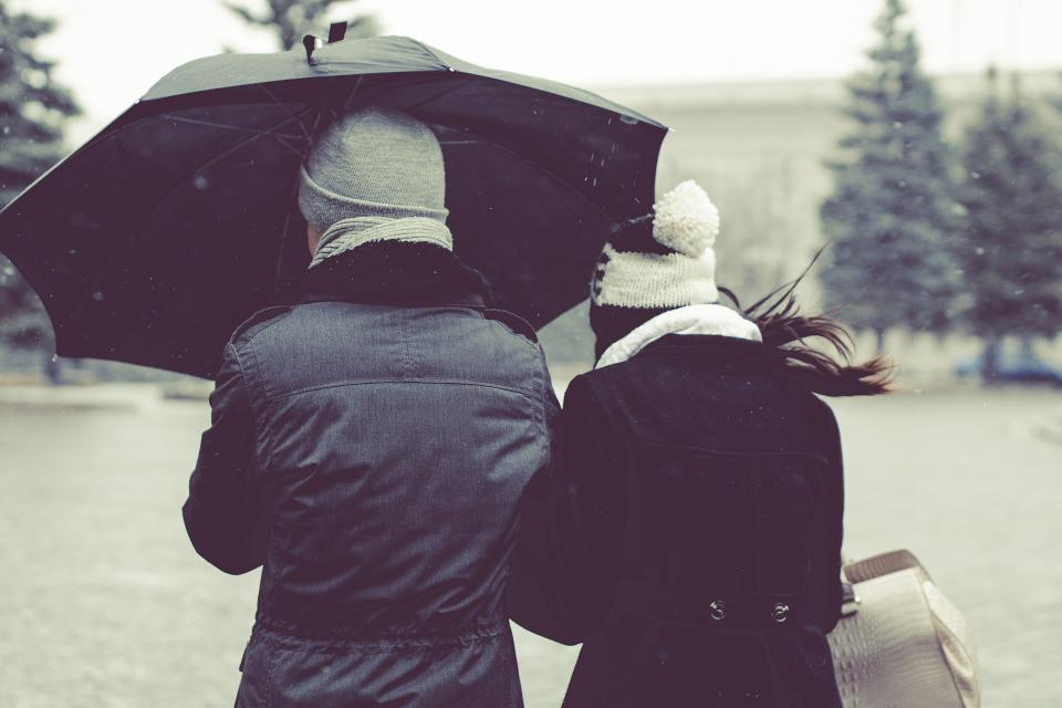 couple holding hands guy man girl woman hat toque fashion coat jacket umbrella cold winter snowing people friends