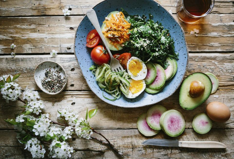 flat lay food salad diet healthy avocado fruits egg vegetables flower white wood drinks plate fork knife
