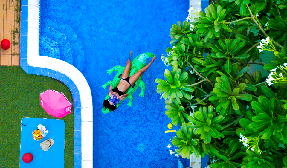 woman pool blue crocodile nflatable tree green pink fake relax chill read bikini girl female