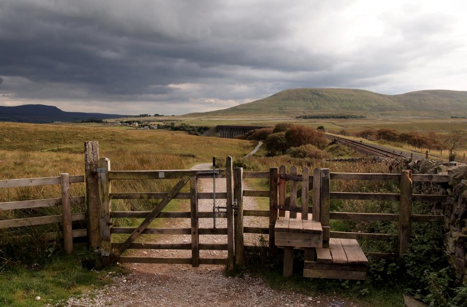 wood fence farm rural countryside grass field hills storm clouds cloudy nature landscape outdoors path