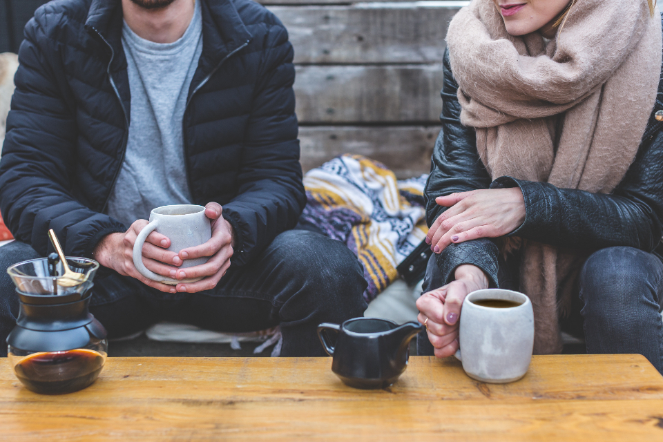 drinking coffee outside man woman female male cold scarf jacket pot black wood panels table drink food