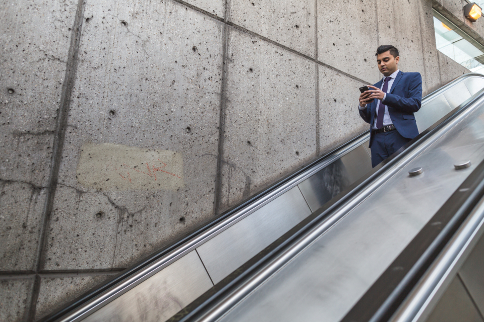 busy businessman escalator mobile phone work travel technology person people up down focus suit fashion