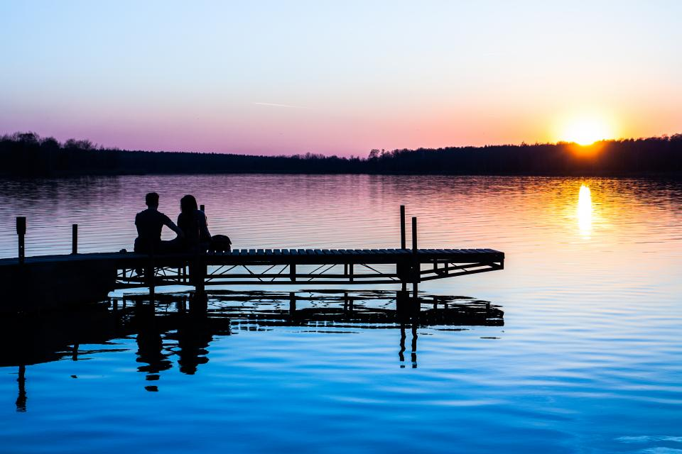 nature landscape sunset people bond date couple man woman hangout shadows silhouette water river lake dock trees travel adventure vacation