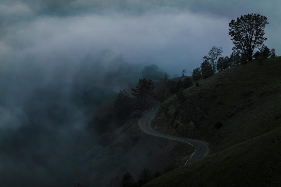 landscape nature mountain highland valley road street trees plants smoke dark sky