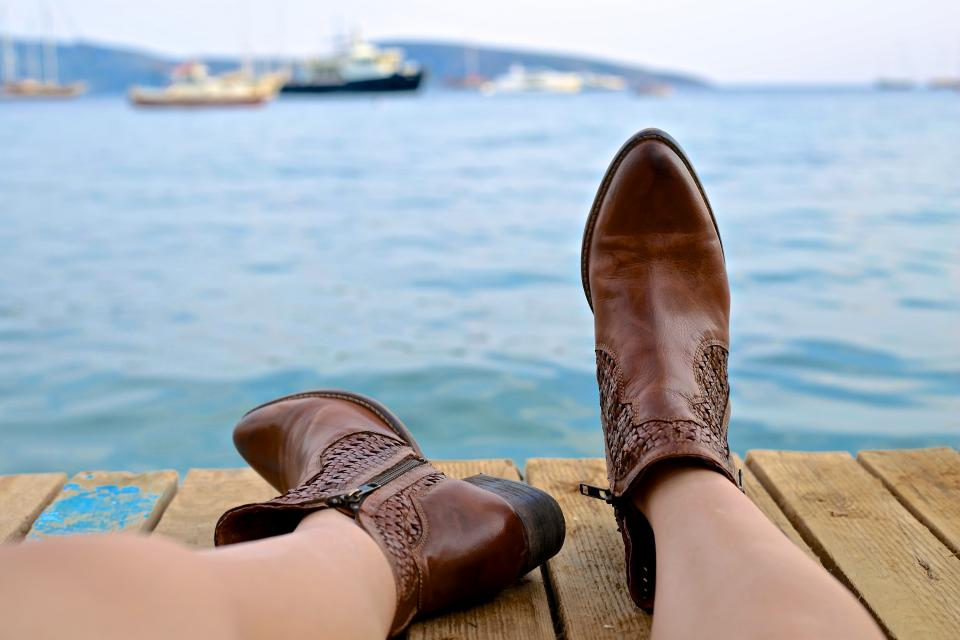 people woman boots leather brown dock wood water ocean sea boat ship