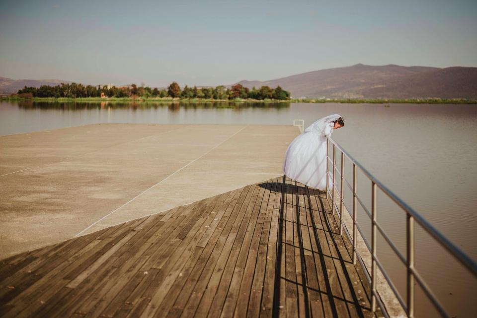 people girl bride wedding gown sea water horizon mountain sky tree plant steel fence pier outdoor