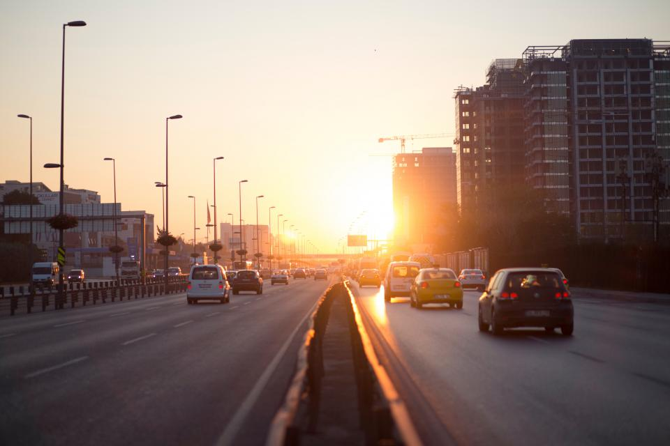 car vehicle lane road transportation pole lights sky city architecture buildings sunset sunrise sunlight sunshine