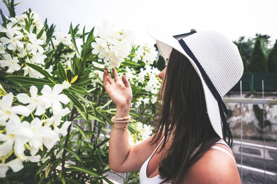 woman smelling flowers nature hat summer summer dress tanned travel vacation white
