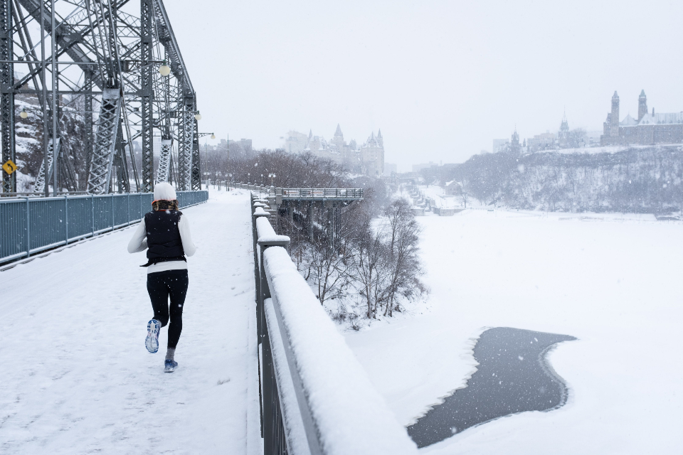 running urban exercise runner winter snowing female bridge path snow cold river ice trees city