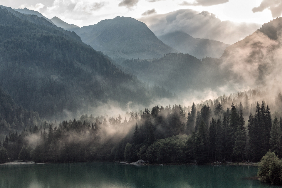 lake lakeside antholz sun rays fog water cottage trees mountains hills mist sunshine