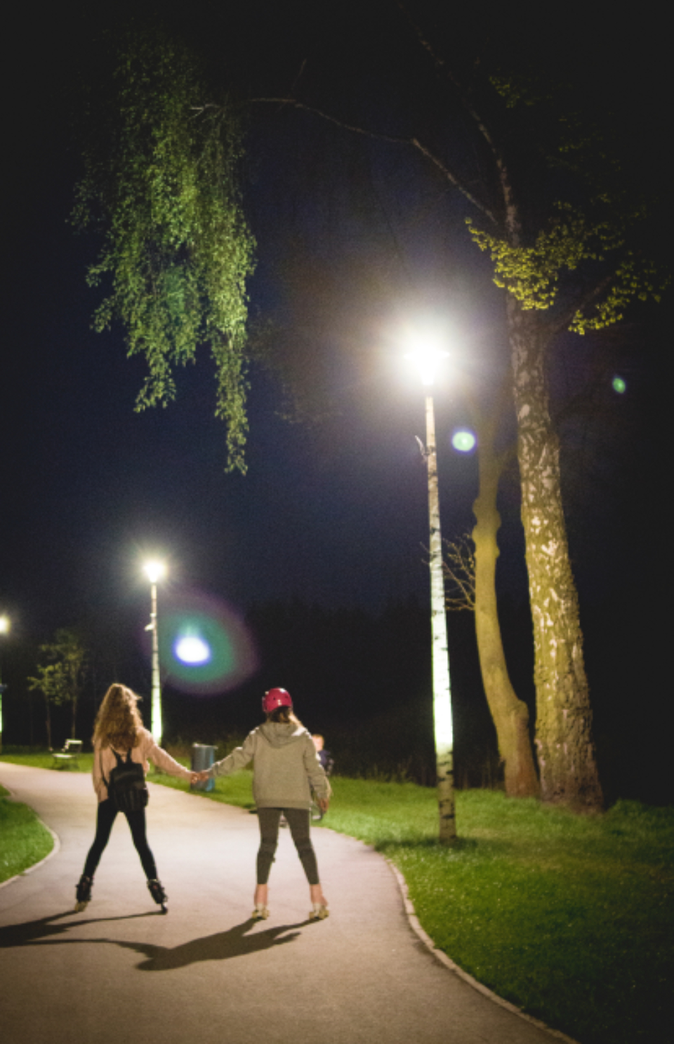 woman rollerblading night couple holding hands street lights palm tree sport fun