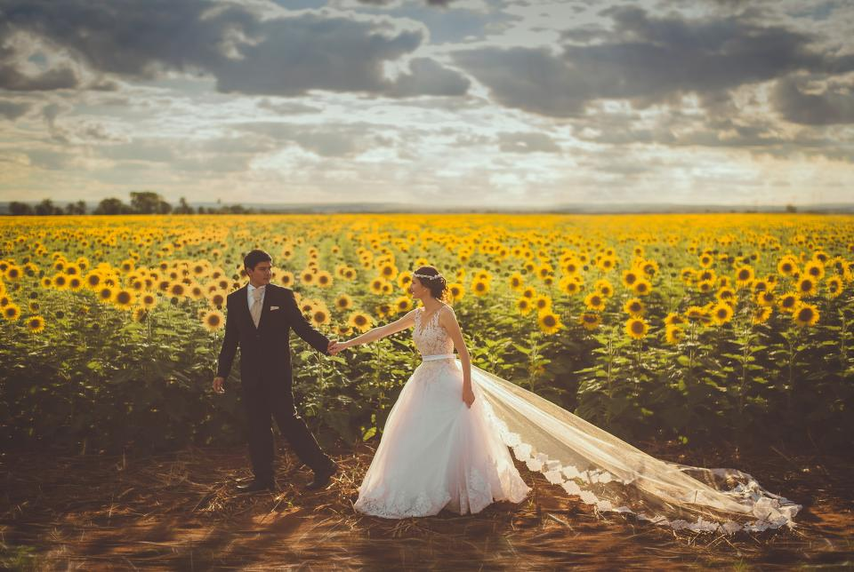 flowers sunflower marriage couple love happy holding hands gown suit wedding field clouds sky man woman people