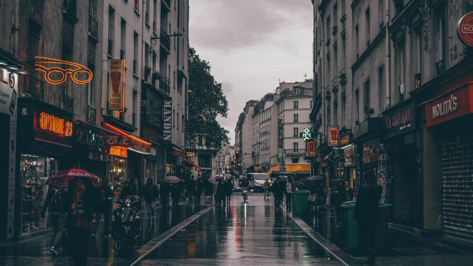 architecture building structure street people restaurants shops rainy wet umbrella men women crowd dark city signage motorcycle car vehicle lights