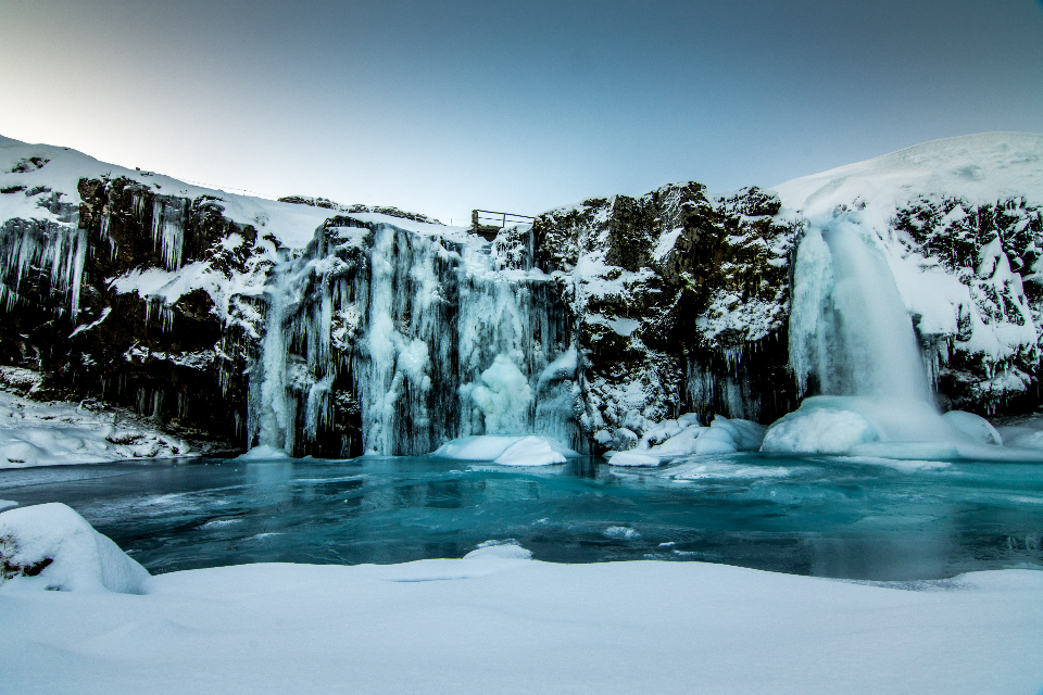 frozen waterfalls iceland winter snow ice cold freezing water nature outside outdoors rocks landscape sky flowing travel