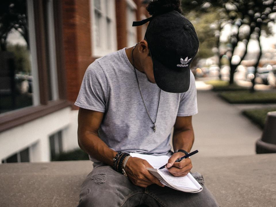 people man guy black cap hat notebook pen write sitting alone outdoor