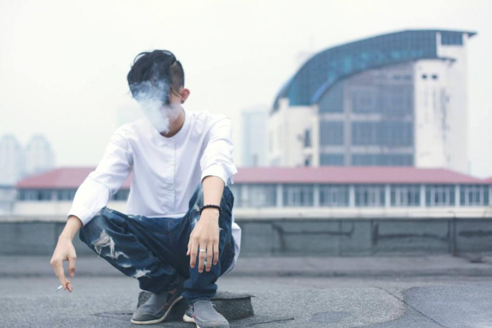 people guy alone sitting smoking cigarette rooftop building blur