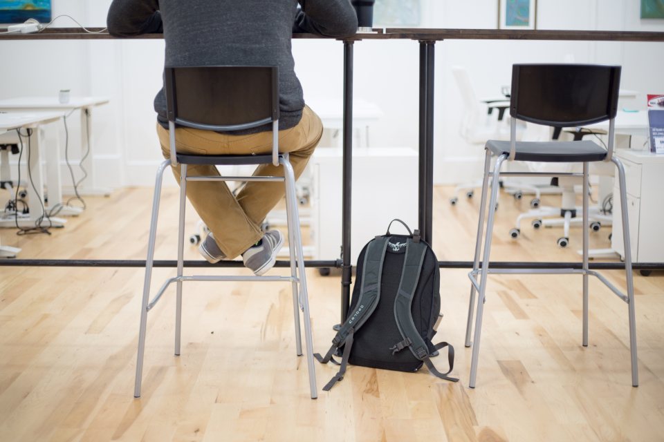 sitting working male desk chair office cafe backpack freelance casual snaeakers technology