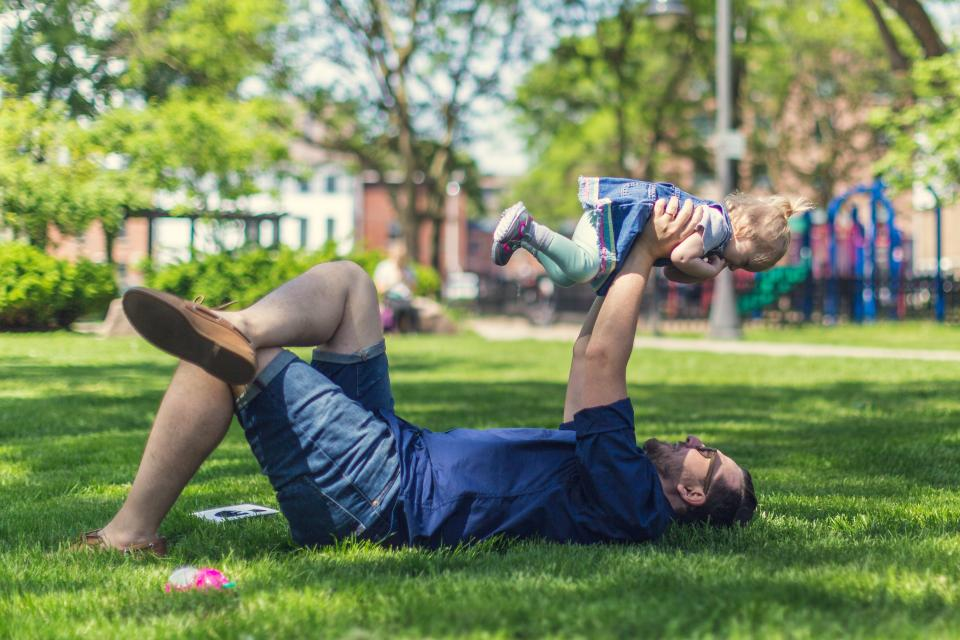 people father man baby girl kid child family bonding love outdoors green grass lawn landscape playground trees plants