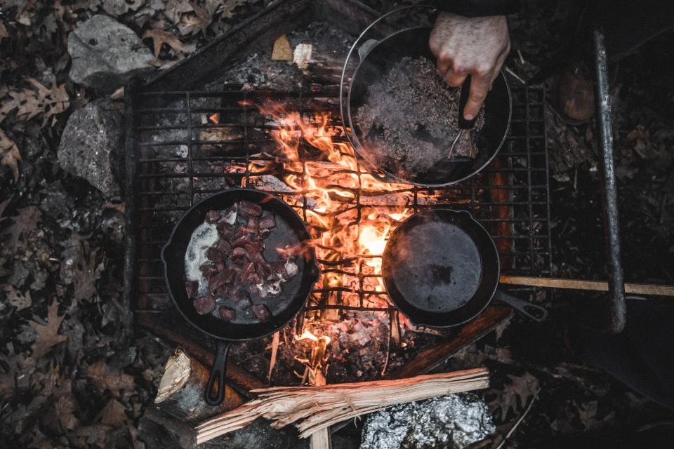 grill camp food tin pans smoke grates flame fire cooking leaves rocks hand
