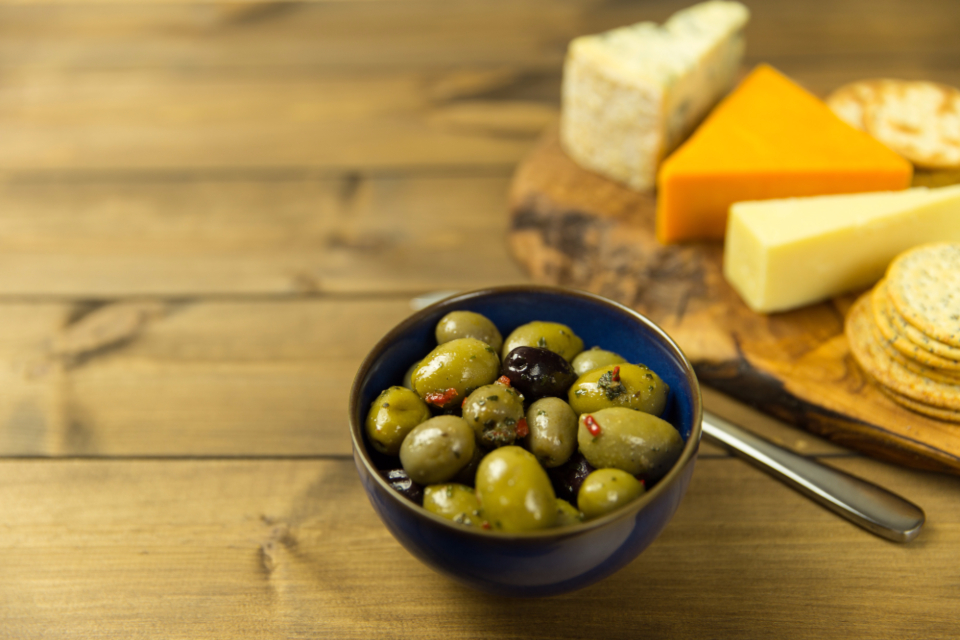 olives cheese crackers table wood spoon bowl food snack