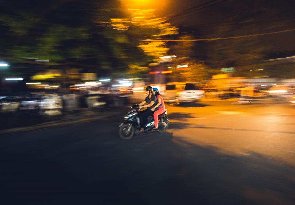 dark night city lights blur people ride motor motorcycle vehicle travel road street
