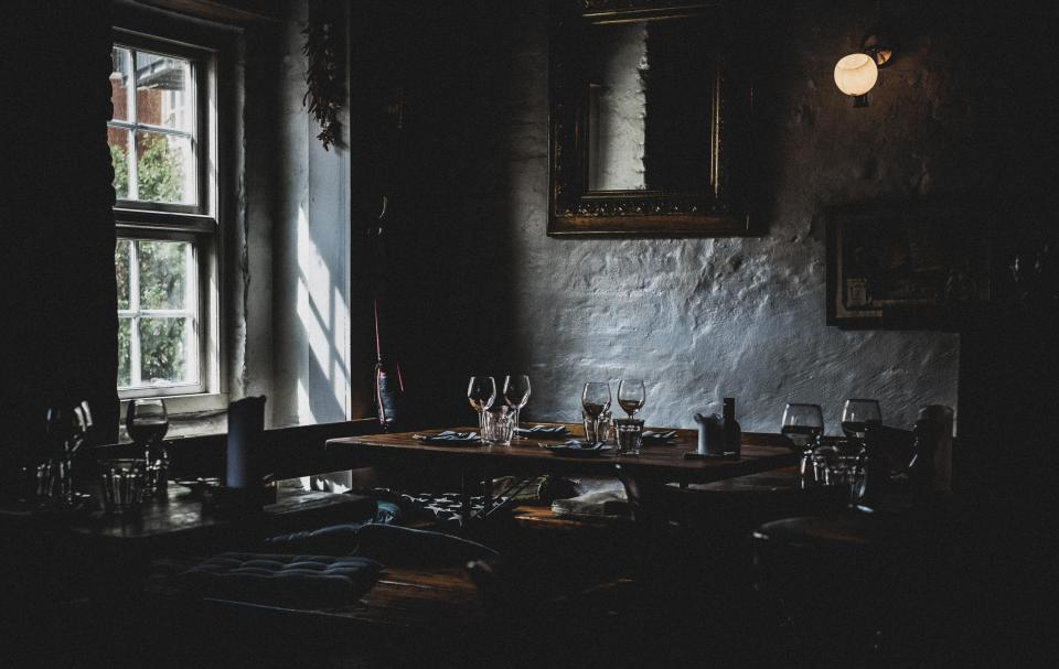 dark restaurant table setup drink wine glass frame window mirror light wall inside