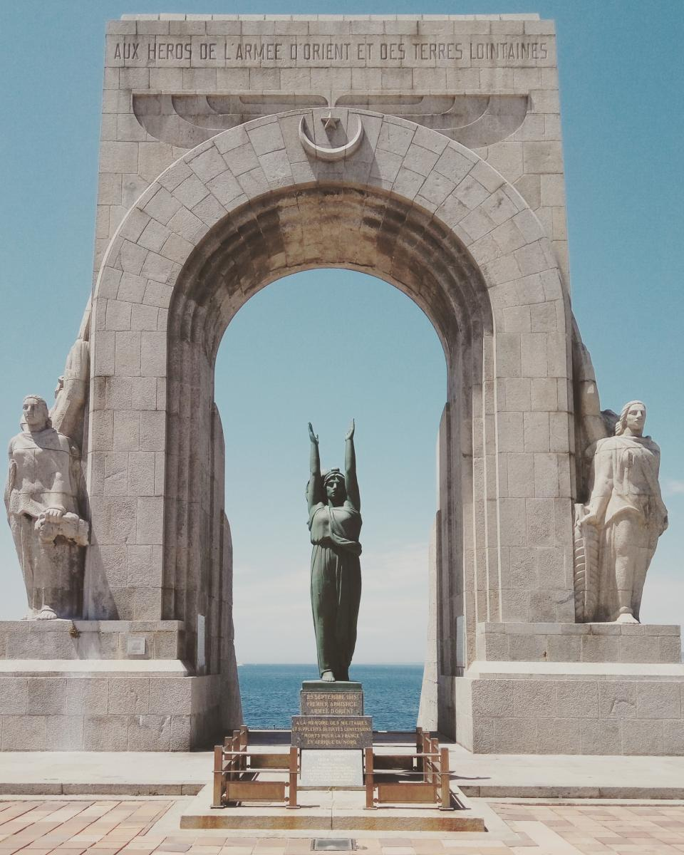 statue sculpture monument gate arch landmark travel coast sea ocean water blue sky