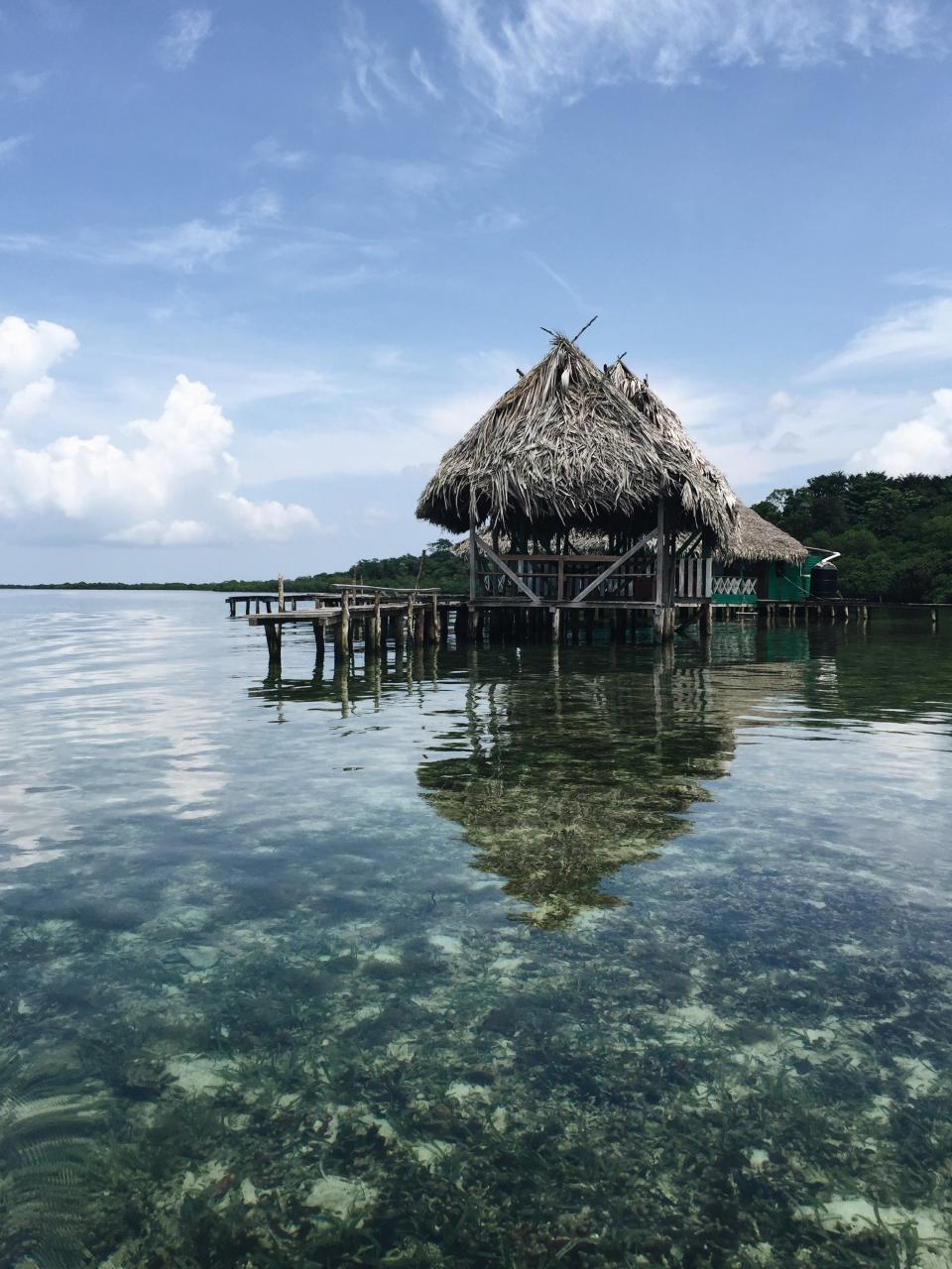hut vacation water clear corals nature reflection sky clouds trees bridge adventure travel