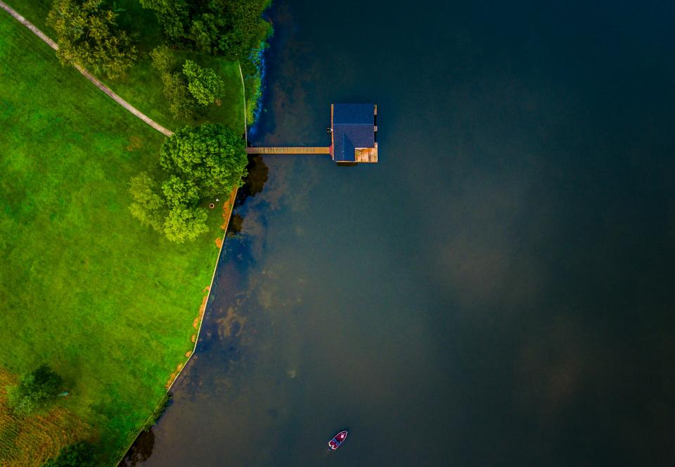 aerial view green grass trees blue lake water boat sailing pathway house roof