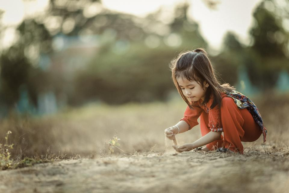people girl child kid alone grass playing sand bokeh