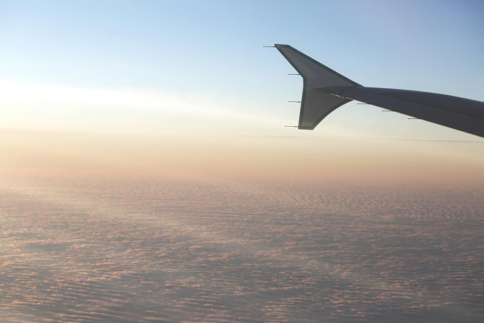 airplane wing flying travel vacation trip transportation aerial view above the clouds sky sunshine